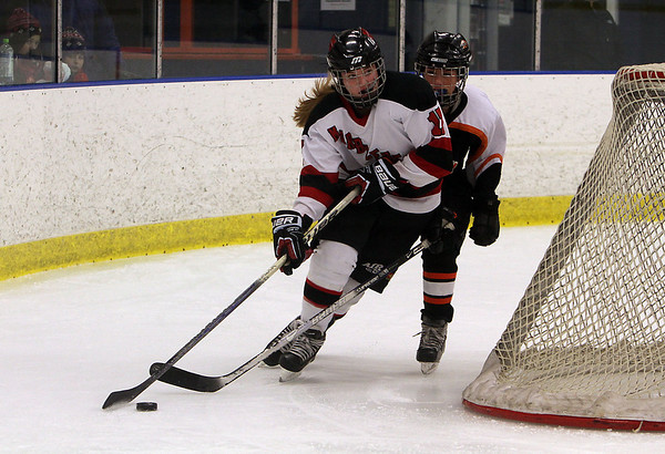 Marblehead's Brittany Smith (17) carries the puck while being hasseled by Beverly's Olivia Konaxis on Saturday. David Le/Salem News