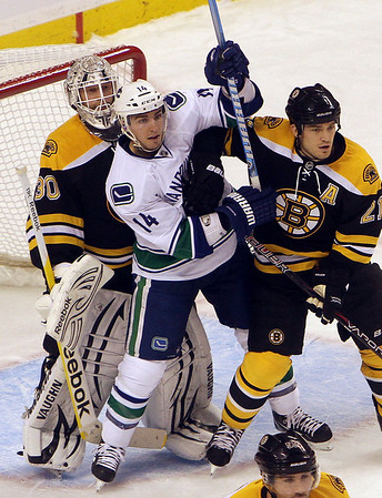 Vancouver forward Alex Burrows gets tangled up with Bruins goalie Tim Thomas and defenseman Andrew Ference. David Le/Salem News