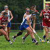 Danvers senior captain Allyson Spencer, right, scoops up a ground ball and takes off down field against Gloucester. The Falcons defeated the Fishermen 13-11 on Tuesday afternoon. David Le/Staff Photo