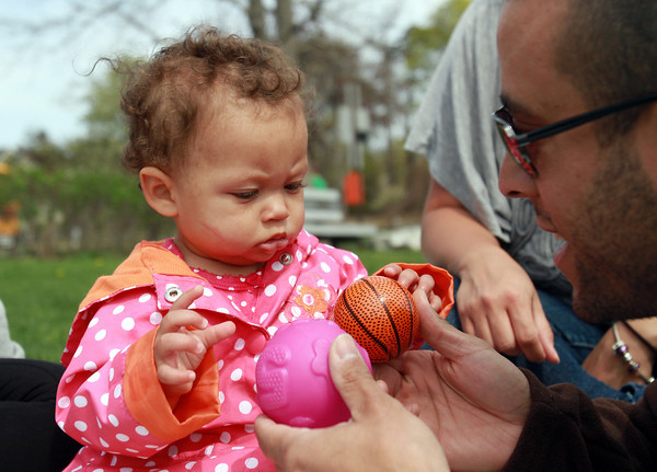 Isabella Jones, 9 months, of Beverly, tries to choose between two different toys from family friend Brian Holmes, of Haverhill, while enjoying an afternoon at Lynch Park on Wednesday. David Le/Staff Photo