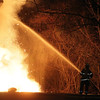 A Beverly firefighter works to put put out a fire that started on the backside of an apartment complex located on Folley Pond Road in Beverly on Wednesday night. David Le/Salem News