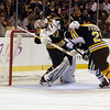 Bruins goalie Tim Thomas gets hit with a high stick by Vancouver forward Mason Raymond as Bruins Andrew Ference closes in. David Le/Salem News