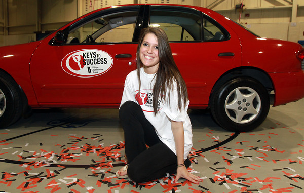 Peabody High School senior Linda Pratto kneels in front of her brand new car which she won from the Keys To Success program. David Le/Staff Photo