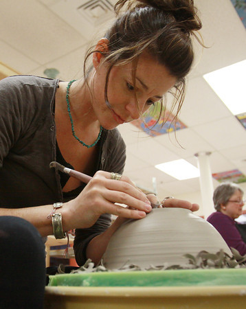 Cory Upton, of Beverly, sculpts a bowl on a pottery wheel at Clay Dreaming Pottery Studio on Wednesday afternoon. David Le/Staff Photo