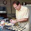 Dan Welch, Co-Director of the Greenhouse School plates some homemade mac and cheese bites in preparation for a fundraiser event to cover expenses from a recent fire. David Le/Staff Photo