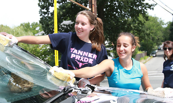 Peabody High School sophomore volleyball players Emily Diezemann, left, and Sabrina D'Angelo, wash cars during a team fundraiser on Saturday afternoon. David Le/Staff Photo