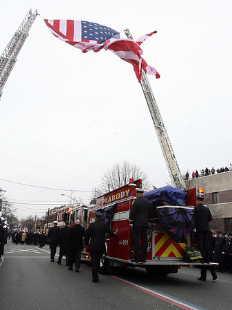 Peabody: Peabody Engine 5, carrying the casket of Peabody firefighter Jim Rice passes under an American flag that was flown in New York City following the September 11th attacks. David Le/Salem News