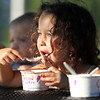 Eliana Brown, 4, of Beverly, is illuminated with bright sunlight as she sits in the shade under a tree and eats ice cream at the Beverly Homecoming Ice Cream Social on Monday evening. David Le/Staff Photo