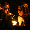 The faces of Kaitlyn Kidney, left, of Salem, and Natasha Hudson, right, of Peabody, are illuminated by candlelight at a vigil remembering Stephanie Moulton, a human service worker who was murdered by a patient last January. David Le/Salem News