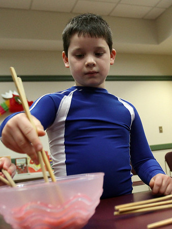 Isaac Hoover, 7, of Hamilton, practices using chop sticks at the Lunar New Year Celebration at the Hamilton-Wenham Public Library. David Le/Staff Photo