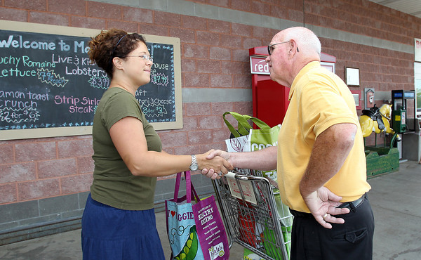 State Senate candidate Ed Carroll talks briefly with Deanna Pierpan, of Beverly, outside the Market Basket on Endicott St. in Danvers on Saturday morning. David Le/Staff Photo