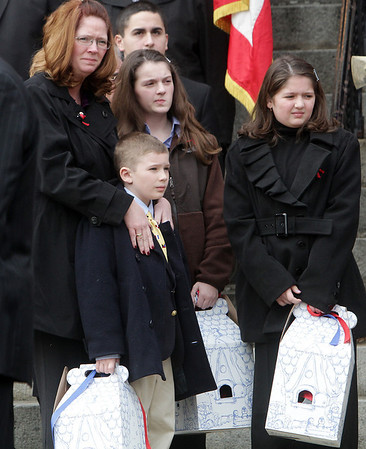 Peabody: Amy Rice, widow of fallen Peabody firefighter Jim Rice, stands with her children, Ryan, 7, Alyssa, 12, and Katelyn, 9, as they watch the casket get loaded onto the back of Peabody Engine 5. David Le/Salem News
