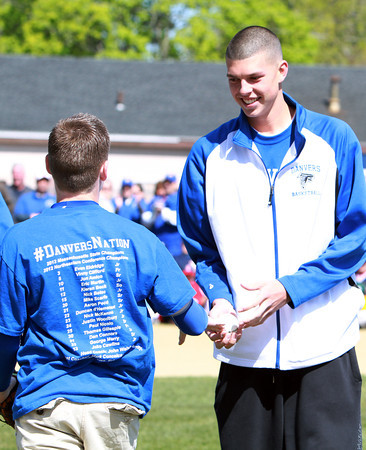 Danvers senior George Merry gets the ceremonial first pitch he threw from Shane Smith, 6th grader and the Danvers High School Basketball Team's ball boy, at the Danvers American Opening Day festivities on Saturday morning. David Le/Staff Photo