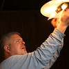 Michael Cram, of Beverly Public Services, works on a light fixture inside the Carriage House at Lynch Park.  David Le/Staff Photo