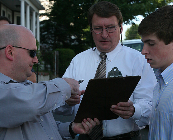 Salem: Dave Crane, left, hands the pen and clipboard with a petition to John Ronan, Counselor of Ward 5 in Salem, as Ronan's son, John Henry Ronan looks on. The petition was started by outraged Salem residents on Ocean Ave. who became aware of a proposed methadone clinic on Canal Street and wanted appropriate measures to be taken to stop the clinic from opening. Photo by David Le/Salem News