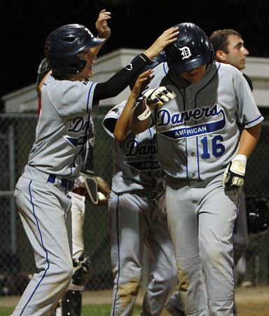 Danvers American's Tim Usalis, left, pounds teammate Zach Dillon on the helmet after Dillon hit a grand slam to stretch out Danvers' lead over Gloucester on Friday night at Harry Ball Field. David Le/Staff Photo