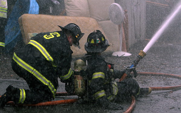 Peabody: Two firefighters work together to try and put out the fire in the backyard of 5 Hancock St. on Friday afternoon. David Le/Salem News