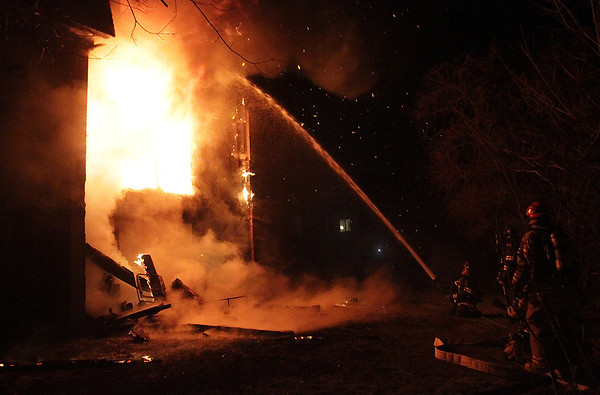 A Beverly firefighter tries his best to fire a massive fire in an apartment complex on Folley Pond road as he waits for help from neighboring fire departments on Wednesday night. David Le/Salem News