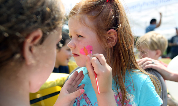 Mia Bazin, 5, right, of Beverly, waits patiently as Giana Roberto, 8, also of Beverly, paints a butterfly on her cheek, at the Beverly Homecoming Lobster Festival on Wednesday. David Le/Staff Photo