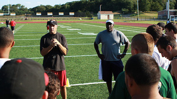 Danvers: A large group of high school football players intently listen to former NFL players Joe Fleming, left, and Vernon Crawford during a free mini camp session held at Bishop Fenwick High School on Tuesday afternoon. Photo by David Le/Salem News