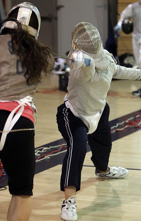 St. John's Prep senior Saber Squad Captain Alex Charow, right, lunges as he fences with Assistant Coach Meredith Steyer, on Thursday afternoon. David Le/Salem News