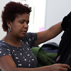 Salem: Mirna Brito, of Peabody, examines articles of clothing at The Salvation Army's indoor yard sale on Saturday afternoon to benefit some of the events The Salvation Army hold there. Photo by David Le/Salem News
