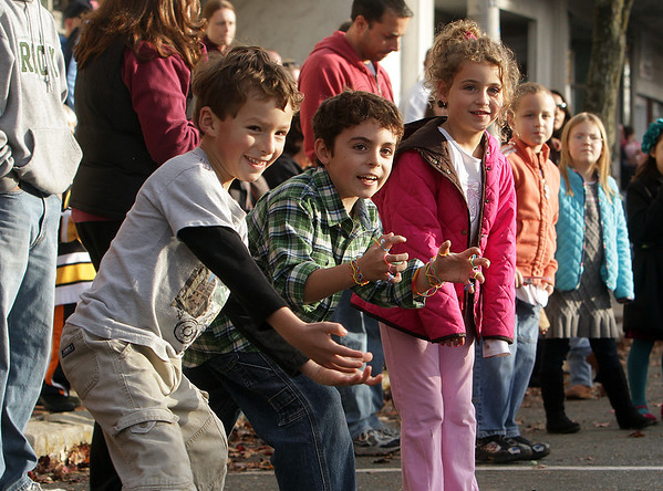 From left, Isaiah Aminzadeh, 5, Max Gomez, 9, and Ella Aieta, 5, all of Beverly, wait to catch candy that was being tossed by paraders on Sunday afternoon.  David Le/Salem News