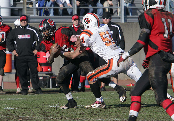 Salem High School quarterback Christian Dunston (15) left, gets dragged down by Beverly's Rob Cattell (51) on Thanksgiving Day. David Le/Salem News