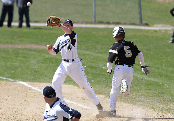 Peabody 2nd baseman Matt McIsaac (4) waits for the ball to arrive at first base as Bishop Fenwick's Nick Bona (5) beats out an infield single on Saturday morning. David Le/Staff Photo