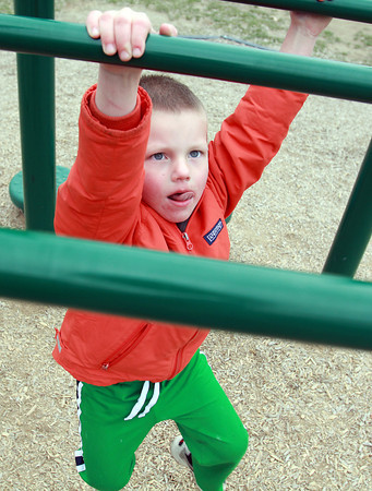 Callan McCay, 4, of Beverly, concentrates as he swings across the monkey bars at Kimball Haskell Park in Beverly on Wednesday afternoon. David Le/Staff Photo