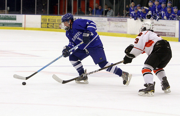Salem: Danvers defenseman Peter Marshall, left, controls the puck while under pressure from Beverly's Kevin Lally, right, on Friday night. David Le/Salem News