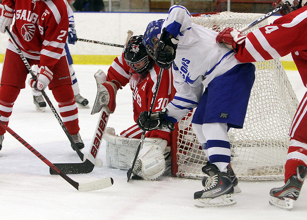 Salem: Danvers sophmore Kevin Hodgkins tries to jam the puck past Saugus goalie Nick Hegarty (30) on Wednesday night, David Le/Salem News