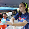 Maura Benson, 16, of Salem, hands customers cups of Italian Ice from Rita's Italian Ice, during the Ice Scream Bowl at Salem Common on Tuesday. David Le/Staff Photo