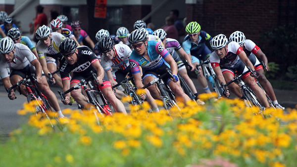 Riders in the Men's Elite Division of the Witches' Cup lean sharply into a turn onto Washington Square East on Wednesday evening. David Le/Staff Photo