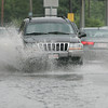 Cars along Bridge St. in Salem splash through a long stretch of flooded street on Tuesday afternoon following a downpour. David Le/Staff Photo