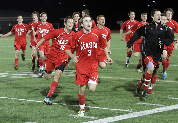 The Masconomet Boys Soccer team led by senior captain Alex Brown (3) run over to celebrate their 2-0 semi-final win with a large crowd of fans on Tuesday night. David Le/Salem News