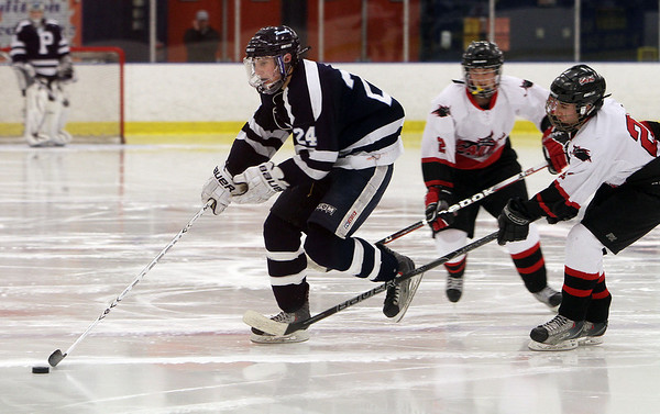Peabody's Nick Salalayko (24) left, speeds up-ice carrying the puck while being pressured by Salem's Matt LeBlanc (24) right. David Le/Salem News