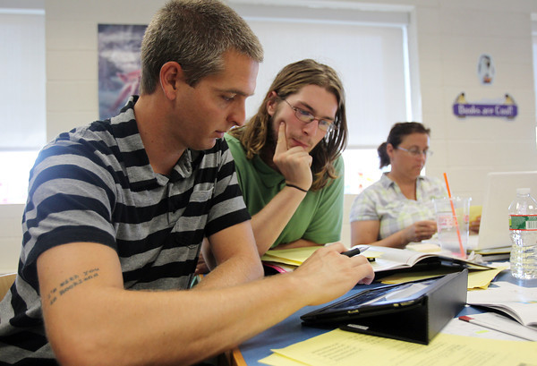 """E2 teacher Stephen Croft, left, and Integrated Science Specialist Greg Sheridan, right, work together to learn a new program on the iPad as part of the new """"innovation school"""" model that the Carlton School in Salem is adopting for the upcoming academic year. David Le/Staff Photo"""