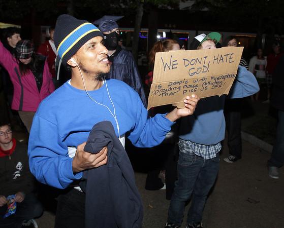 Jose Briceno, of Boston, holds up a sign near a religious rally held on the street corner near Gulu Gulu on Halloween night. David Le/Staff Photo.
