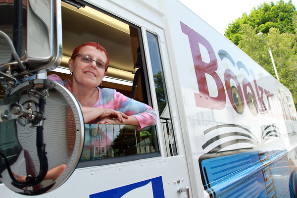 Linda Caravaggio, BookMobile Librarian for the past 25 years, leans out of the window of their brand new BookMobile which has arrived at Beverly Public Library. David Le/Staff Photo