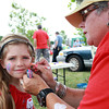 Lily Ferguson, 5, of Danvers smiles as she gets her face painted by Barbara Kritikos, of Salem, at a fundraiser for Salem Play Areas for Canine Exercise, at Leslie's Retreat Dog Park in Salem on Saturday morning. David Le/Staff Photo