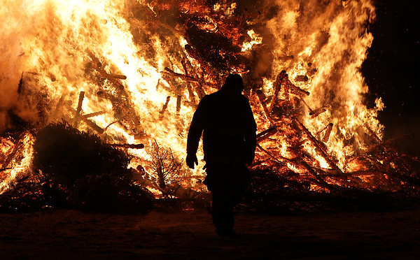 Salem firefighter Aaron Bingham walks away from a massive pile of burning Christmas trees after adding another one to the inferno. David Le/Salem News