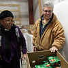 Donna McKenzie, left, Office Manager for St. Joseph's Food Pantry and Program Director Carl Lento, right, organize food in the store room at Joseph's Storehouse, located in the old service department of the former HIllcrest Chevrolet on Highland Ave in Salem. David Le/Salem News