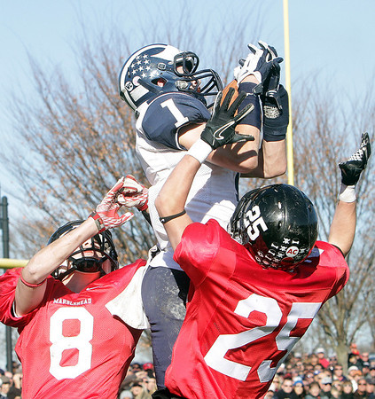 Swampscott senior wide receiver AJ Baker (1) soars over Marblehead's Bing Bial (8) and Zac Cuzner (25) to snag a football on Thanksgiving Day. David Le/Salem News