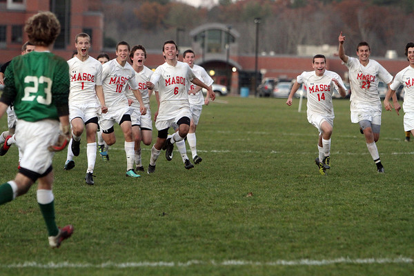The Masco Boys Soccer Team run out to greet goalkeeper Derek Grammer, after he came up with multiple big saves in a penalty shootout to propel the Chieftans to the semi-finals of the MIAA state tournament. David Le/Salem News