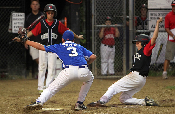 Marblehead's Ben McCarthy, right, slides safely into home plate ahead of a tag from pitcher Nick DiMarino during the Gallant Tournament Final. David Le/Staff Photo