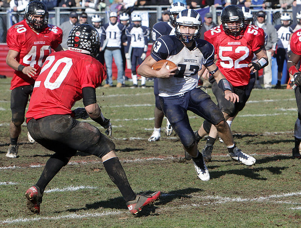 Swampscott quarterback Mike Walsh (13) looks for running room as Marblehead's Will Quigley (20) closes in. David Le/Salem News