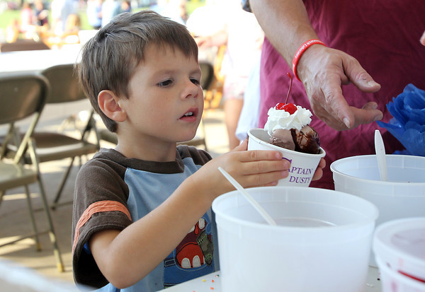 Timonthy Packard, 4, of Beverly, carefully inspects his ice cream after a cherry was placed on top at the Beverly Homecoming Ice Cream Social on Monday evening. David Le/Staff Photo