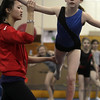Masconomet gymnast and Yellowjackets instructor Julia Small, left, helps Caitlyn Tucker, right, with proper form. David Le/Staff Photo.