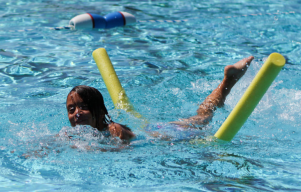Salem: Carly Murphy, 7 of Salem, happily swims across the Forest River Park pool with the help of a noodle during a free swimming lesson on Thursday afternoon. The Forest River Park pool offers free swimming lessons to all Salem residents. Photo by David Le/Salem News